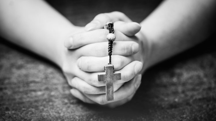 Woman praying with a rosary. Christian symbol. Faith, belief and prayer.