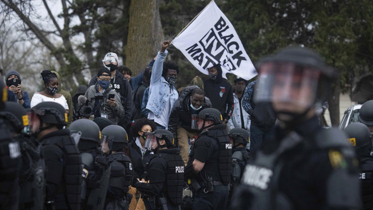 Protesters clash with police near the site where a family said a man was shot and killed by local law enforcement, Sunday, April 11, 2021, in Brooklyn Center, Minn. (AP Photo/Christian Monterrosa)